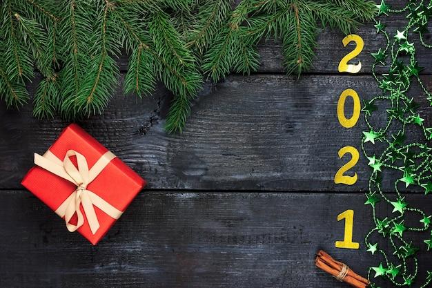 Presente de ano novo em um invólucro vermelho sobre um fundo escuro de madeira com vista superior de ano novo com ramos de pinheiro
