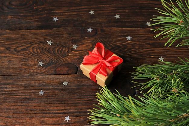 Presente de ano novo em uma caixa perto do ramo de abeto peludo e confetes de natal. em madeira.