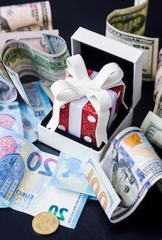 Presente de brinquedo vermelho, dólares e euros em fundo preto