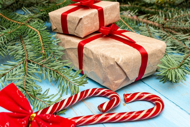 Presente de caixa de presente, doces de natal com laço vermelho na pele de abeto, fundo de ramos de pinheiro close-up