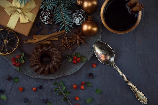 Presente de clima de natal com brinquedos bolinho de chocolate especiarias e frutas xícara de café com canela. vista do topo