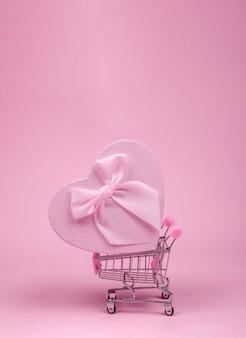 Presente de coração rosa com laço para o dia dos namorados no carrinho de compras