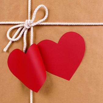 Presente de dia dos namorados com etiqueta de presente de forma de coração vermelho, pacote de papel pardo