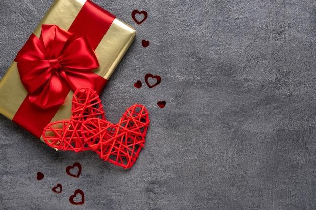 Presente de dia dos namorados com uma fita vermelha e dois corações vermelhos em um fundo cinza de concreto. conceito de dia dos namorados. cópia do espaço. vista de cima.