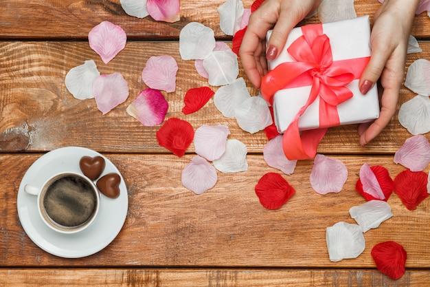 Presente de dia dos namorados e mãos femininas na mesa de madeira