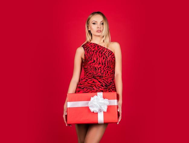 Presente de dia dos namorados. mulher de vestido vermelho com caixa de presente. mulher na moda com roupas de estampa animal. feriados.
