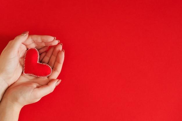 Presente de dia dos namorados. vista superior do coração de feltro feito à mão em uma senhora com as mãos vermelhas