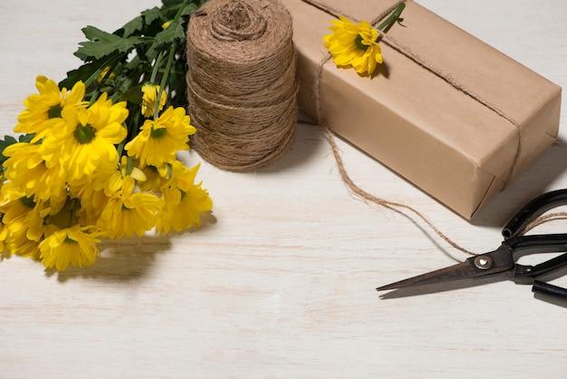 Presente de embrulho de flores sobre fundo de madeira. vista superior com espaço de cópia