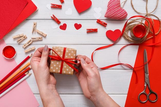 Presente de embrulho em caixa de presente, corações, papel artesanal, tinta e ferramentas de bricolage em madeira branca