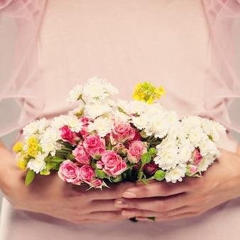 Presente de flores nas mãos de mulher. fundo floral rosa