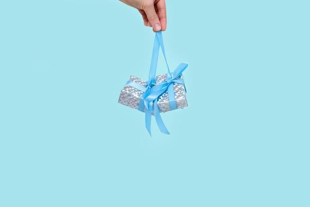 Presente de natal azul com uma fita azul na mão de uma mulher pairando no ar