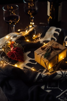 Presente de natal com camisola de malha, luzes de natal e dois copos de vinho.