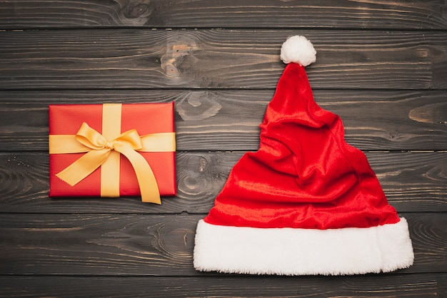 Presente de natal com chapéu em fundo de madeira