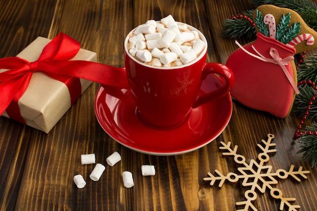 Presente de natal com fita vermelha, chocolate quente com marshmallows no copo vermelho e biscoitos de gengibre no fundo de madeira marrom