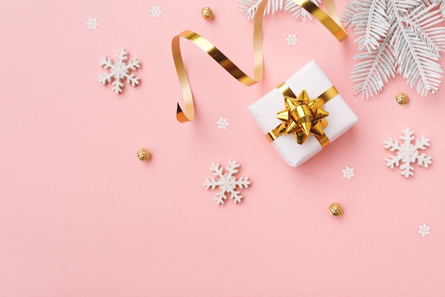 Presente de natal com flocos de neve e decoração em superfície rosa pastel