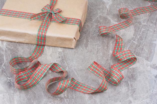 Presente de natal com laço festivo em fundo de mármore.