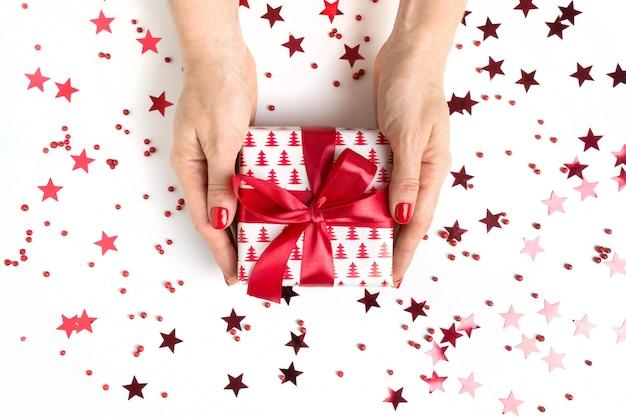 Presente de natal com laço vermelho na mão feminina com estrelas vermelhas e brilhos. natal. . postura plana.