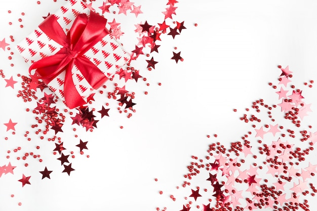 Presente de natal com laço vermelho no fundo branco com estrelas vermelhas e brilhos. banner de natal. feliz ano novo. estilo liso leigo.