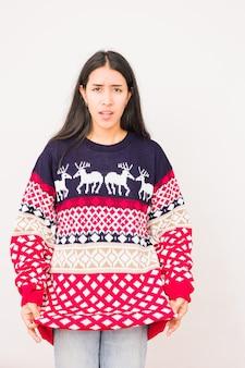 Presente de natal desapontado, suéter feio, expressão infeliz e louca de uma latina presente