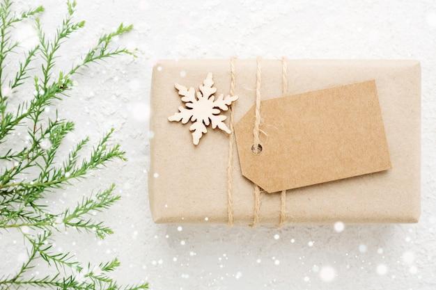 Presente de natal e etiqueta com coníferas no cartão branco nevado