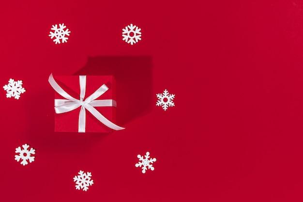 Presente de natal e flocos de neve em um fundo vermelho conceito de venda de ano novo