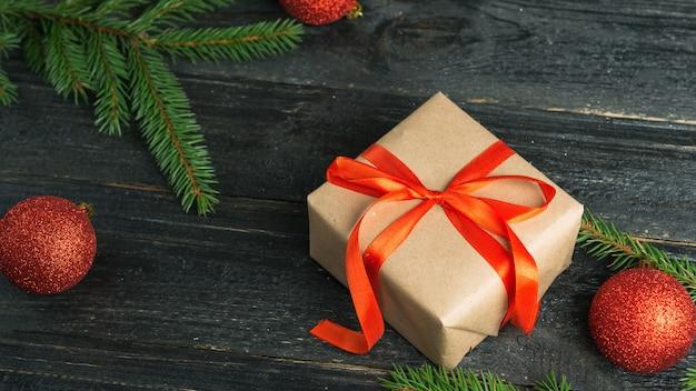 Presente de natal em cima da mesa com galhos de árvores de natal