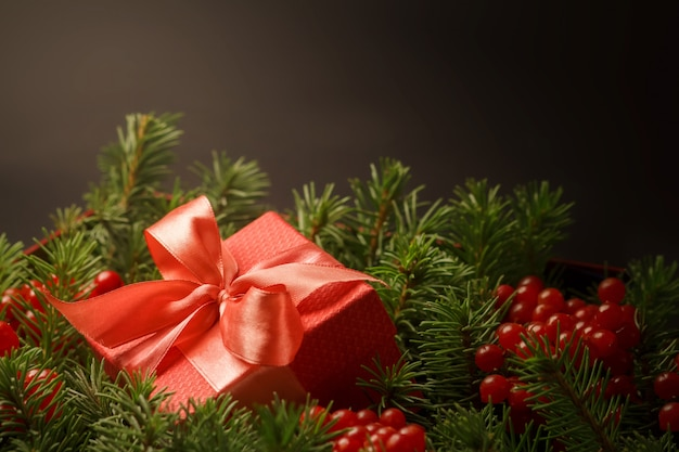 Presente de natal em uma caixa de presente vermelha com uma fita coral imersa nas agulhas de uma árvore de natal.