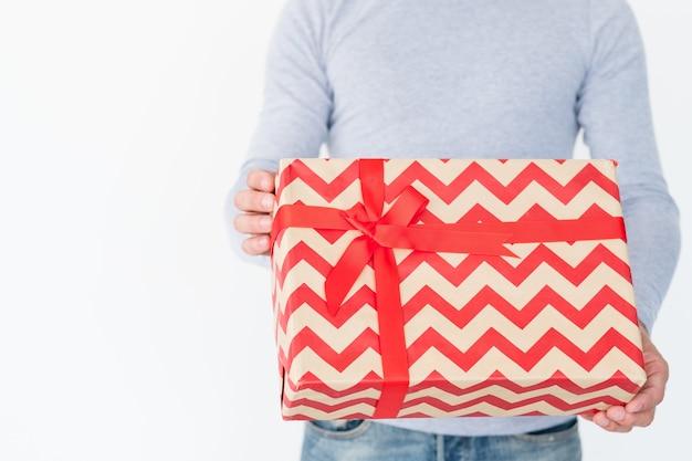 Presente de natal em uma grande caixa de presente com padrão chevron vermelho e um laço