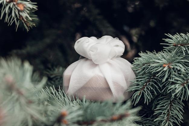 Presente de natal embrulhado com tecido branco furoshiki nos ramos de abeto. presente amigável de eco.
