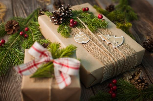 Presente de natal embrulhado em papel kraft com decoração em um fundo de madeira rústica de cima.