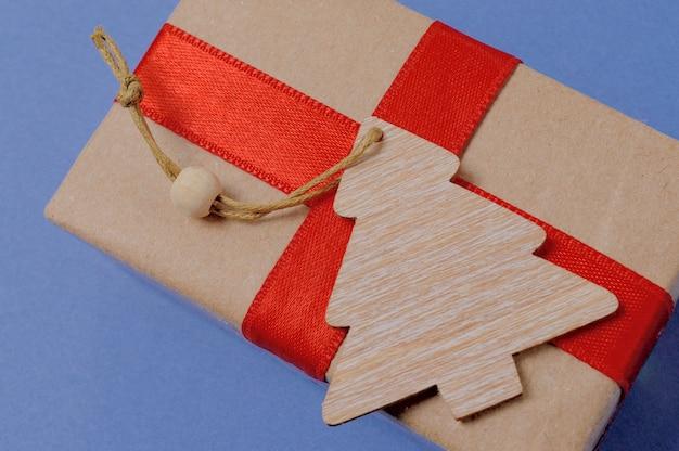 Presente de natal feito de papel artesanal e enfeites de madeira