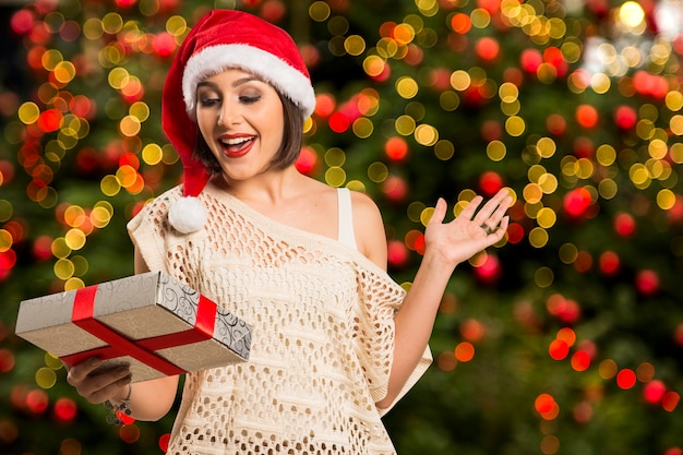 Presente de natal. mulher surpresa com luzes de bokeh de natal