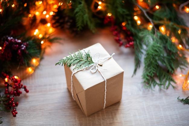 Presente de natal na mesa com decoração do feriado e luzes de guirlanda, design ecológico, close-up.