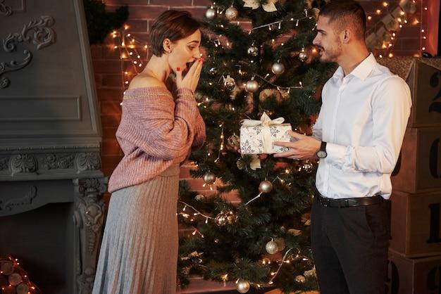 Presente de natal para a mulher. cavalheiro de terno clássico dá a sua esposa o presente