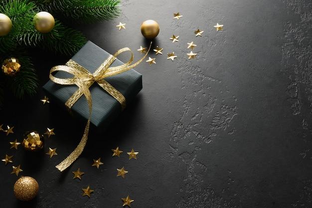 Presente de natal preto com fita dourada decorativa na superfície preta.
