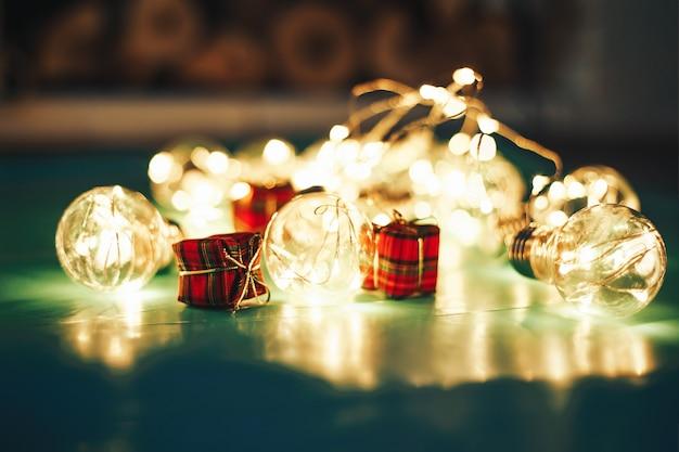 Presente de natal vermelho com espaço de cópia. caixa de natal com luzes de fadas e decorações.