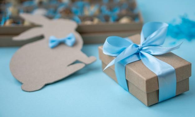 Presente de páscoa com uma fita azul. uma caixa com ovos de páscoa e um coelhinho da páscoa em azul