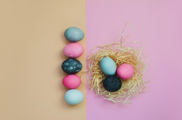 Presente de páscoa, linha de ovos de páscoa na superfície amarela e rosa