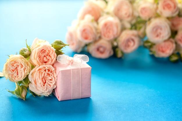 Presente-de-rosa ou caixa de presente e flores de rosas em azul b