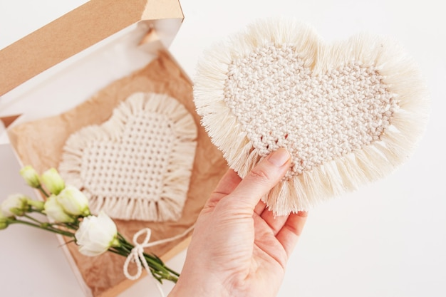 Presente de são valentim com decoração macramê. coração. materiais naturais, fios de algodão. decorações de macro eco, enfeites, decoração feita à mão na mão de uma mulher.