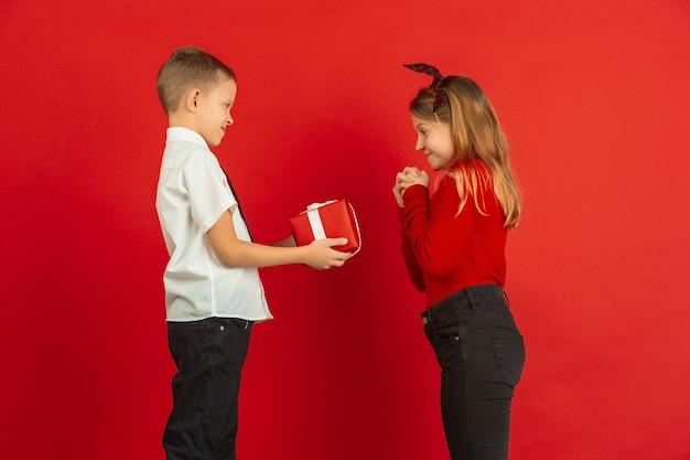Presente deslumbrante. celebração do dia dos namorados, crianças brancas felizes e fofas isoladas no fundo vermelho do estúdio. conceito de emoções humanas, expressão facial, amor, relações, férias românticas.