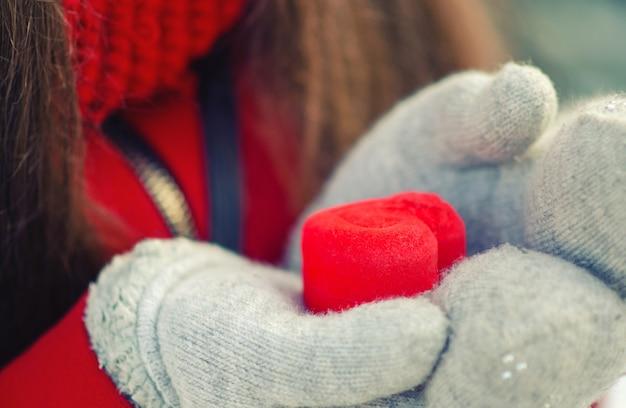 Presente do dia dos namorados em uma caixa vermelha em forma de coração em luvas.