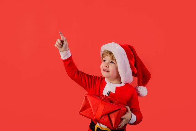 Presente do papai noel ajudante do duende garotinho fantasiado de papai noel com presente do papai noel presentes feliz ano novo