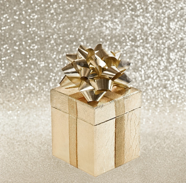 Presente dourado com fita sobre fundo brilhante desfocado