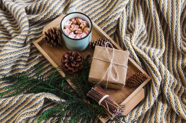 Presente e bebida perto de galho de coníferas e cones no cobertor