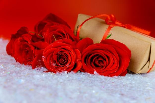 Presente e buquê de lindas rosas vermelhas na neve cintilante. conceito de dia das mães ou dia dos namorados.