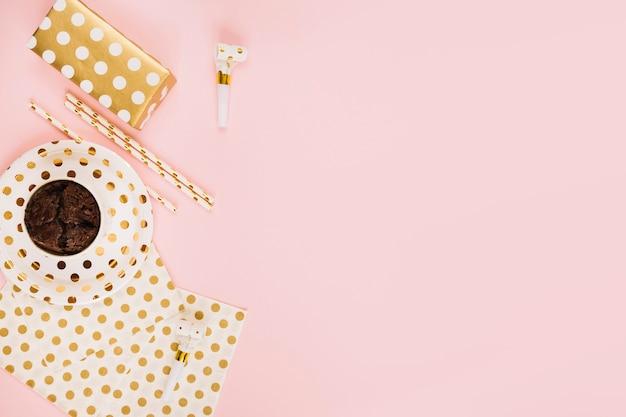 Presente e cupcake perto de palhas e chifre de festa