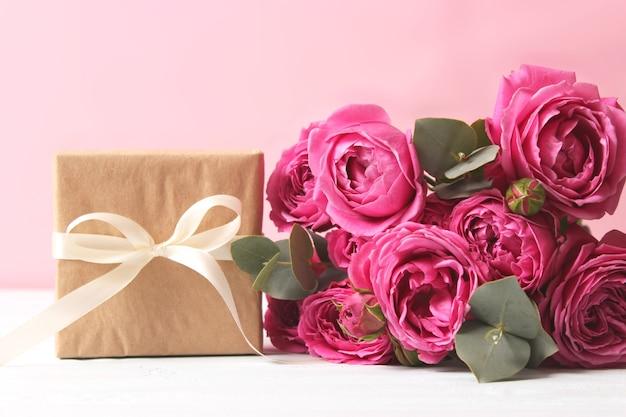 Presente e flores em um feriado com fundo colorido dar um presente parabéns
