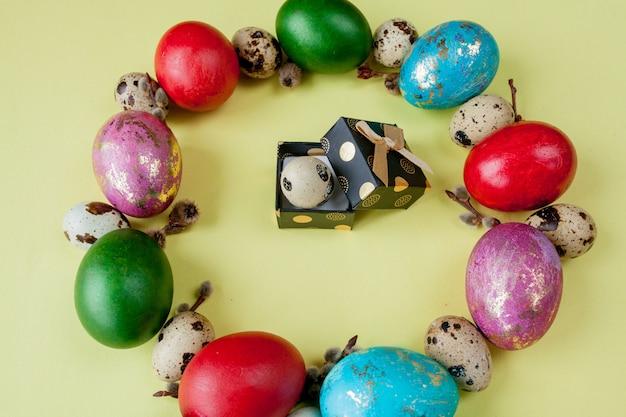 Presente e ovos pintados páscoa frame em forma de círculo sobre um fundo amarelo. copie o espaço, vista superior