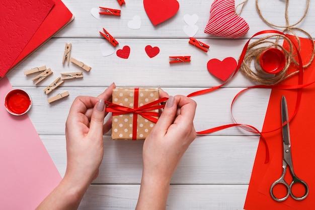 Presente em caixa de presente criando, corações, papel artesanal, pintura e ferramentas diy em madeira branca